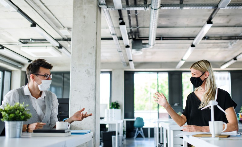 Employees wearing masks in the office and social distancing