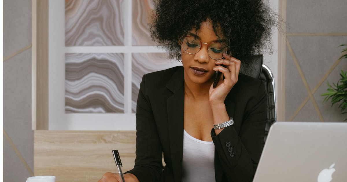 Woman writing while on the phone